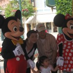 Mickey Mouse and Minnie Mouse characters posing for a picture with an Asian family