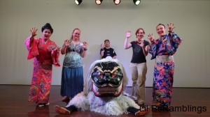 My sister and I posing with the men in the shisa dog costume and the lady dancers.