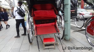A red and silver two seat carriage pulled by a man.