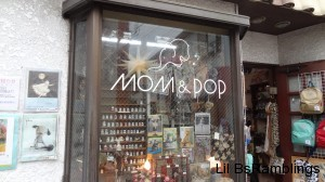 A shop window with vintage looking items behind glass that says MOM&POP
