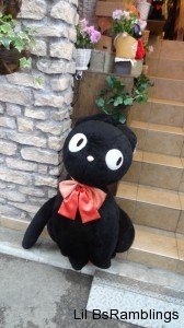 A large stuffed black cat similar to the one in Kiki's Delivery Service leans on a wall next to stairs