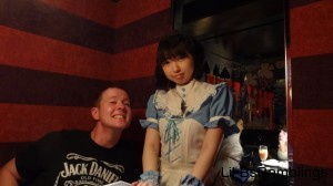 My friend John posing with the waitress dressed in a blue Alice dress.