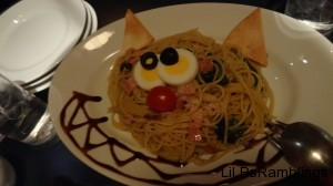A plate of yellow noodles with bread for ears, eggs and olives for eyes, a cherry tomato for a nose, and sauce on the side forming a Cheshire Cat grin.