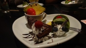 An illusion of a snail is created with green cakes cut with whip cream between and chocolate antlers next to a slice of chocolate pie, a slice of pinapple, and a strawberry.