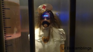 A plastic figure stands behind glass in a nurse outfit but with its heart removed.