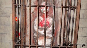 A plastic mummy highlighted with blood behind aged bars.
